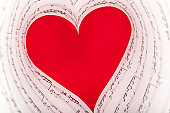 close up of a still life assembly of music sheet against red textile in the form of a heart, real setting,not photomontage, selective focus,copy space,sheet is prelude of J.S.Bach